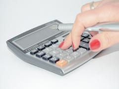 Picture of a woman's hand punching numbers in a calculator.